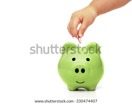 baby's hand putting a golden coin into a green piggy bank - young generation doing green saving concept - stock photo
