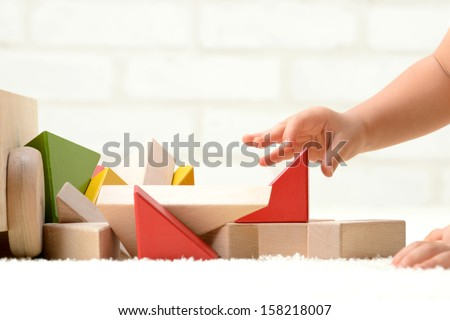 Baby's hands playing with building blocks - stock photo