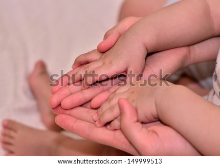 Baby's small hand on mommy's big hand - stock photo