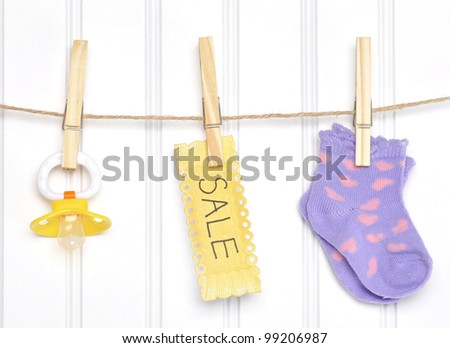 Baby Sale Goods on a Clothesline Socks Pacifier Dummy. - stock photo