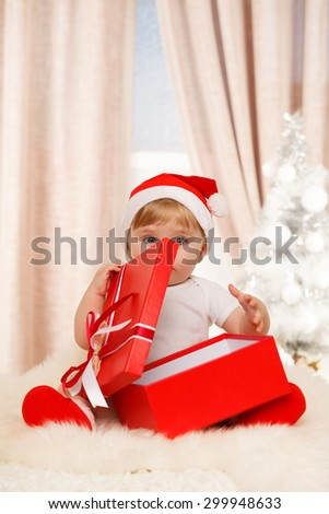 Baby santa holds a big red gift box - stock photo