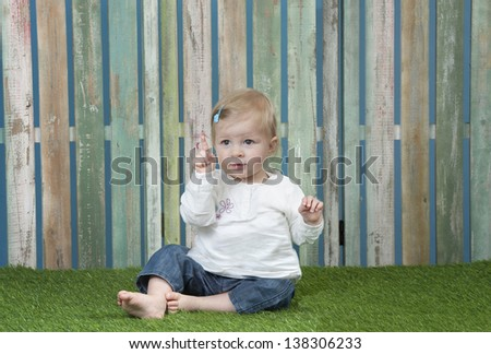 baby seated on grass in front of a weathered fence saying no - stock photo
