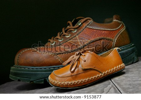 baby shoe against adult boot - stock photo