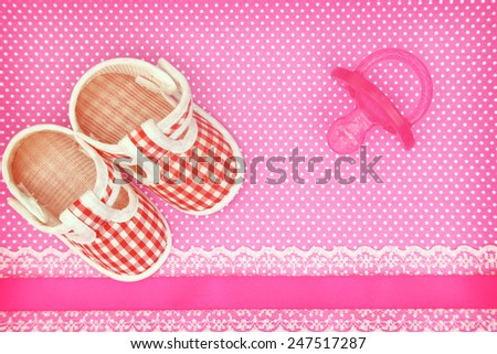 Baby shoes and pink pacifier on polka dots background with copy space - stock photo