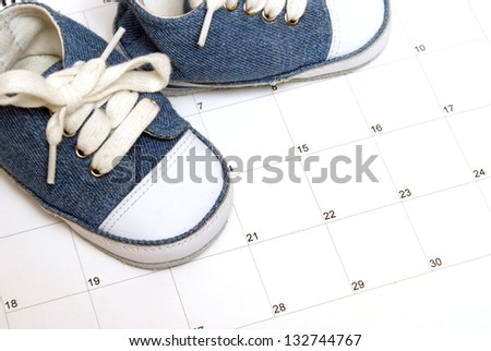 Baby shoes on a calendar for many scheduling representations. - stock photo