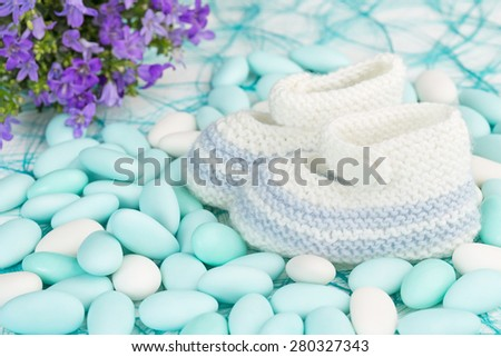 baby shoes on white and blue sugared almonds - stock photo