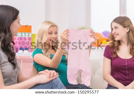 Baby shower. Beautiful pregnant woman receiving gifts from her friends - stock photo