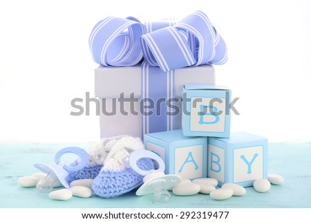 Baby shower Its a Boy blue gift, with gift box, baby booties and dummy on pale blue shabby chic rustic wood table.  - stock photo