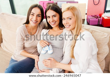 Baby shower. Top view of happy young pregnant woman holding baby booties on her abdomen and smiling while two friends sitting close to her on the couch  - stock photo