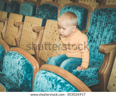 Baby sitting in a theatre - stock photo