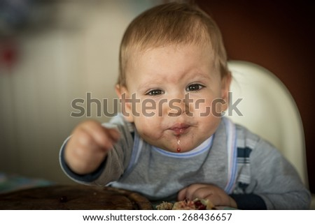 baby sitting in baby chair and eating - stock photo