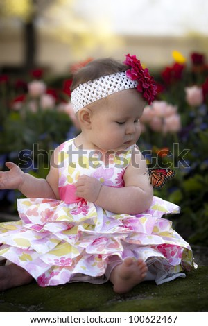 Baby sitting in flower garden looking at butterfly on her arm - stock photo