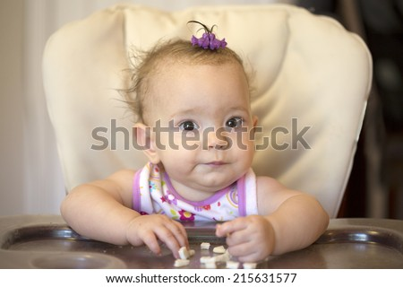Baby sitting in high chair with crackers, looking at camera - stock photo