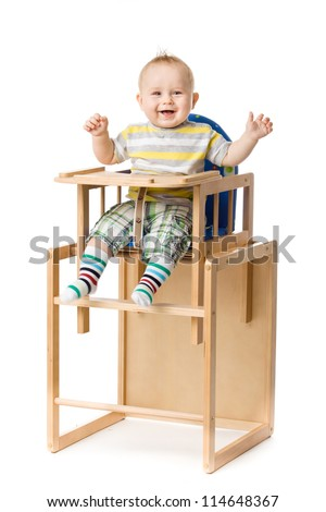 Baby sitting in highchair. - stock photo