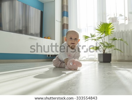 baby sitting in sunny living room on the ground and playing with teddy bear - stock photo