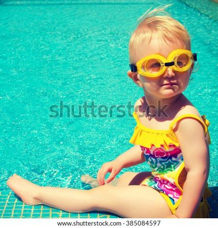 Baby sitting near swimming pool. - stock photo