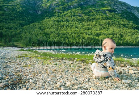 Baby sitting on a rocky beach of a mountain lake and looking around his shoulder - stock photo