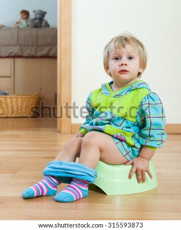 Baby  sitting on potty in home interior - stock photo