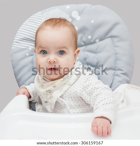 Baby sitting on the grey highchair and waiting for food. Baby looking straight at the camera. Selective focus on baby head. - stock photo