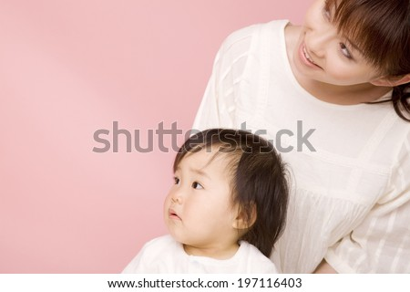 Baby Sitting On The Lap Of Mother - stock photo