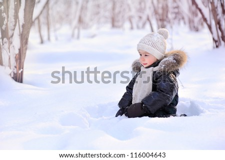 baby sitting on the snow in the woods - stock photo
