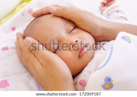 Baby sleeping and father hand  - stock photo