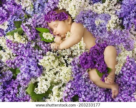 baby sleeping, newborn child on flowers background holding leaf in hand  - stock photo