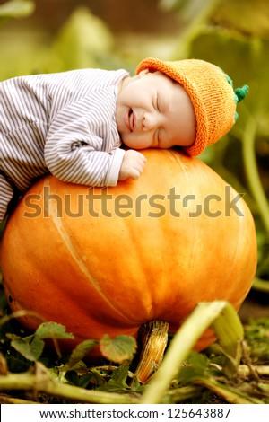 baby sleeping on big pumpkin - stock photo