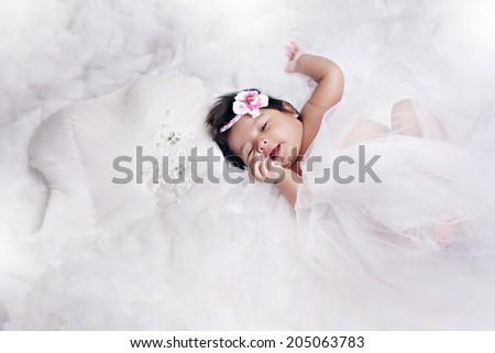 baby sleeping on wedding dress - stock photo