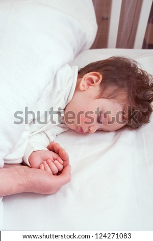 Baby sleeping peacefully in her crib - stock photo