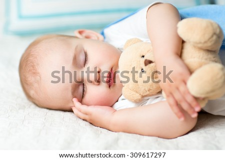 baby sleeping with fluffy toy on bed - stock photo