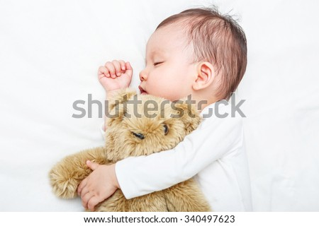 Baby sleeping with her teddy bear, new family and love concept (Soft focus and blurry) - stock photo