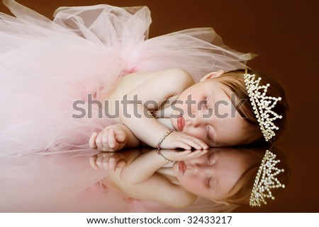 baby sleeping with tutu and crown - stock photo