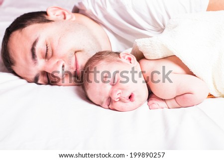 Baby sleeps with dad - tender care of his father - stock photo