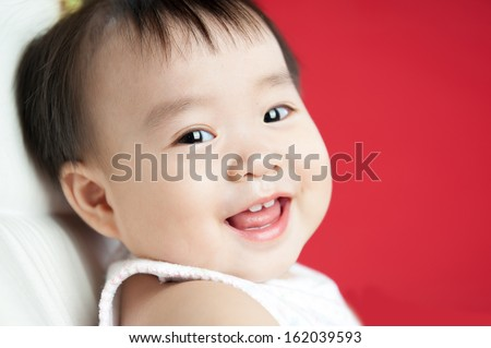 baby smiling and looking up to camera isolated on red background - stock photo
