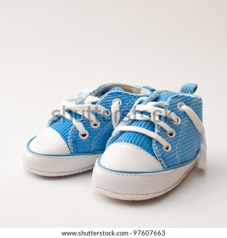 Baby sneakers. Pair of blue and white baby sneakers over gray background - stock photo