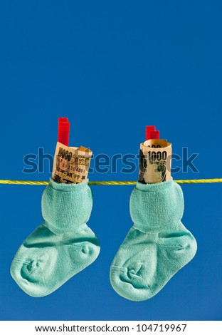 baby socks on clothesline with yen banknotes from japan. - stock photo