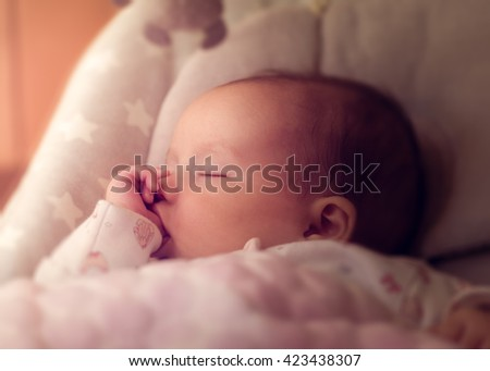 Baby sucking thumb in the sun - stock photo