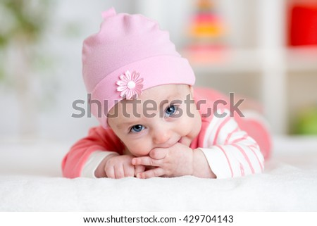 Baby teething sucks fingers. Infant kid lying in nursery - stock photo