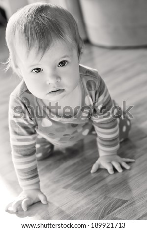 baby to crawl on the floor and with interest looking at the camera ( black and white ) - stock photo