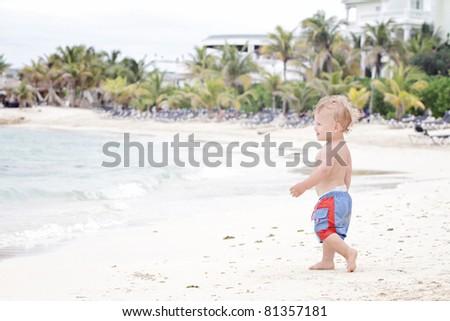 Baby, toddler boy having fun running on a tropical beach - stock photo
