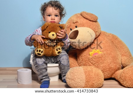 Baby toddler sitting on the potty and playing with toilet paper. Cute kid potty training for pee and poo and surrounded by teddy bears, car and lots of toys - stock photo