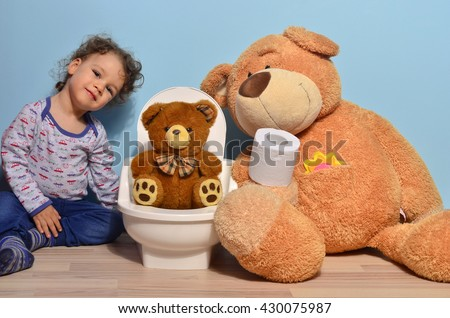 Baby toddler sitting on the potty and playing with toilet paper. Cute kid potty training for pee and poo and surrounded by teddy bears - stock photo