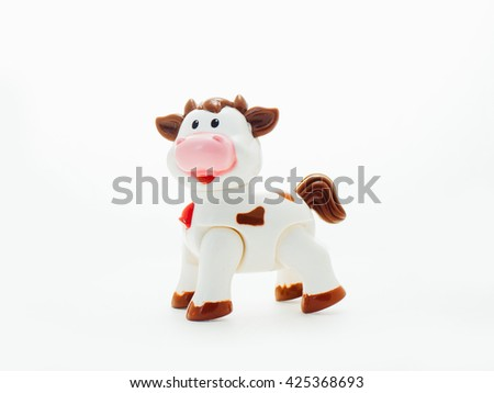 Baby toy cow made of plastic isolated on white background. Cute children toy cow on white background. - stock photo