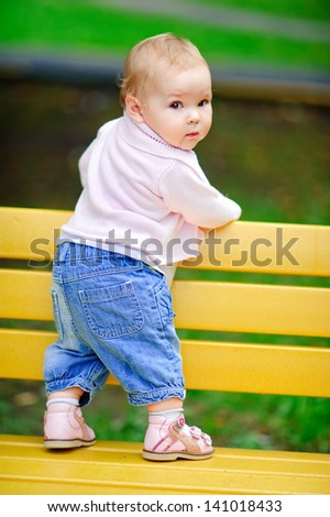 Baby try to stand and learning walking. First step. - stock photo