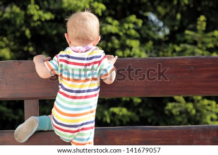 Baby trying to go through the fence - stock photo