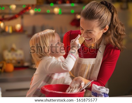 Baby trying to smear mothers nose with flour while making christmas cookies - stock photo