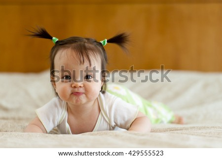 Baby tummy time with funny facial expression - stock photo
