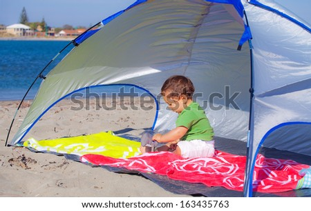 Baby under a beach shelter   - stock photo