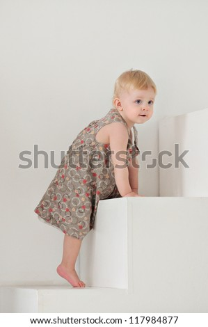 Baby up the white stairs. On a small child brown dress. - stock photo